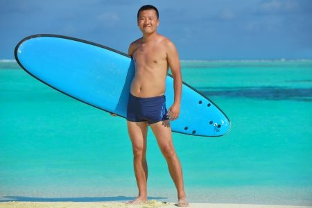 Man with surf board on beautiful tropical beach  beach photo