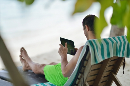 business travel: business man relaxing and use tablet computer at beautiful tropical beach Stock Photo