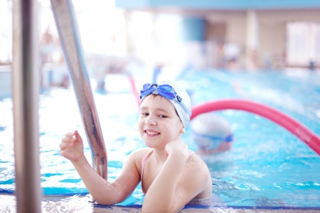 school sports: happy children kids group  at swimming pool class  learning to swim