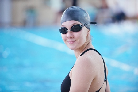 Happy muscular swimming woman  wearing glasses and cap at swim pool and represent health and fit concept
