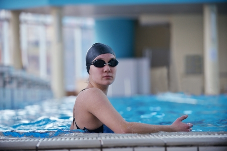 Happy muscular swimming woman  wearing glasses and cap at swim pool and represent health and fit concept photo