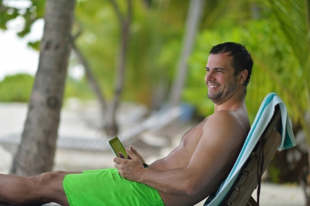 laptop outside: business man relaxing and use tablet computer at beautiful tropical beach Stock Photo