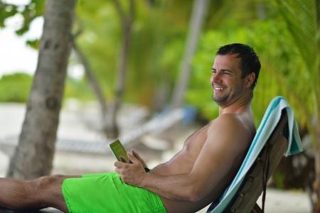 fiestas electronicas: hombre de negocios de relax y el uso de tablet PC en la hermosa playa tropical