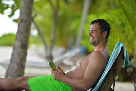 business man relaxing and use tablet computer at beautiful tropical beach Stock Photo - 19649946