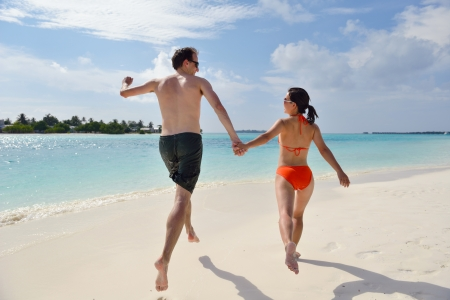 happy young romantic couple in love have fun running and relaxing on beautiful beach photo