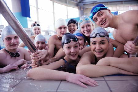 Fat kid: happy teen  group  at swimming pool class  learning to swim and have fun
