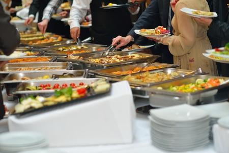 recepcion: grupo de personas catering comida tipo buffet en el restaurante de lujo interior con carne las frutas y verduras de colores Foto de archivo