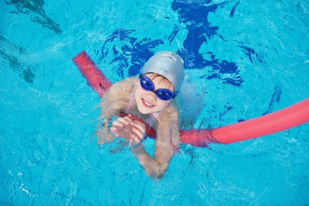 swim goggles: happy children kids group  at swimming pool class  learning to swim