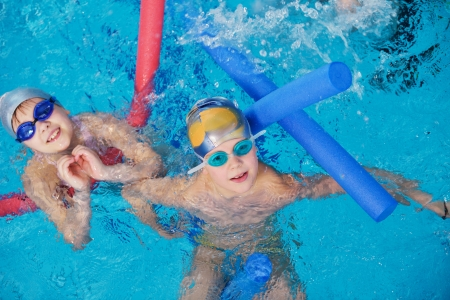 nadar: feliz grupo de ni?os hijos en clases de nataci?n de la piscina para aprender a nadar Foto de archivo