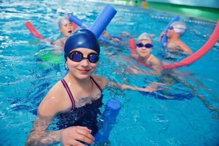 swim goggles: feliz grupo de ni?os hijos en clases de nataci?n de la piscina para aprender a nadar Foto de archivo