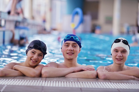 indoors: happy teen  group  at swimming pool class  learning to swim and have fun