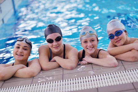 ni�os nadando: grupo de j�venes felices en clase piscina para aprender a nadar y divertirse Foto de archivo