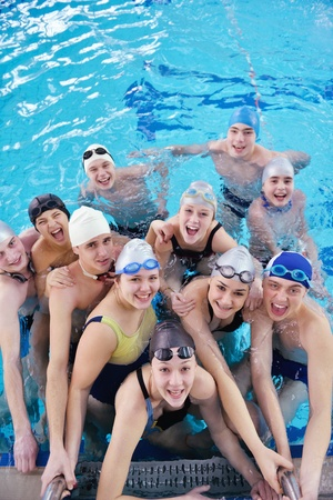 happy teen  group  at swimming pool class  learning to swim and have fun photo