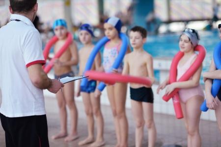 ni�os nadando: feliz grupo de ni�os hijos en clases de nataci�n de la piscina para aprender a nadar