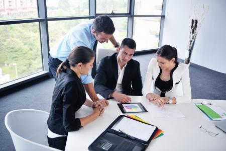 Groep van gelukkige jonge mensen uit het bedrijfsleven in een vergadering op het kantoor van Stockfoto