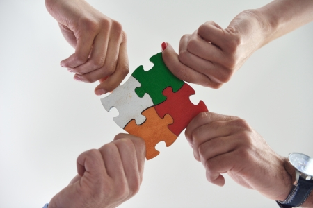 red puzzle piece: Group of business people assembling jigsaw puzzle and represent team support and help concept