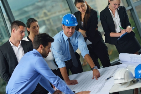 business people group on meeting and presentation  in bright modern office with construction engineer architect and worker looking building model and blueprint planbleprint plans photo