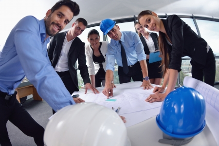 helmet construction: business people group on meeting and presentation  in bright modern office with construction engineer architect and worker looking building model and blueprint planbleprint plans Stock Photo