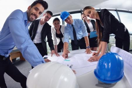 gerente: la gente de negocios del grupo en la reunión y la presentación en la oficina de moderno y luminoso con construcción arquitecto ingeniero y trabajador en busca de modelo de construcción y planes planbleprint modelo