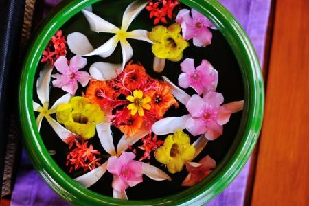 terapia de grupo: taza de agua con hermosas flores, una variedad de colores de fondo en la salud spa y centro de belleza