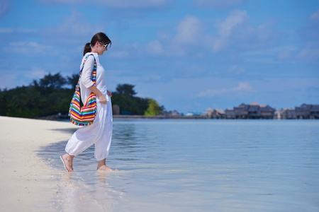 Mujer joven feliz en vacaciones de verano en la hermosa playa tropical divertirse disfrutar y relajarse photo