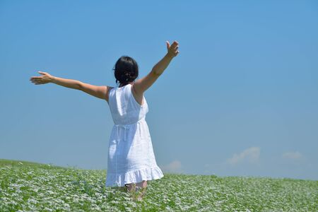 healthy Happy  young woman with spreading arms, blue sky with clouds in background  - copyspace photo