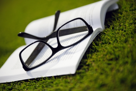 Glasses on a book outside with grass inbbacground, education relax and study concept photo