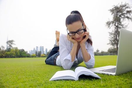gelukkige jonge student vrouw met laptop in stadspark studie Stockfoto