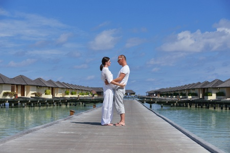 travel location: happy young couple have fun and relax at summer vacation on background maldives travel location and beautiful white sand beach Stock Photo