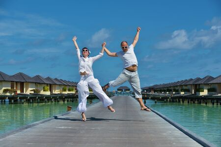 happy young couple have fun and relax at summer vacation on background maldives travel location and beautiful white sand beach photo