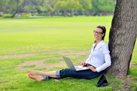 field study: happy young student woman with laptop in city park study