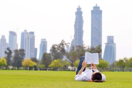 Young student woman reading a book and study in the park photo