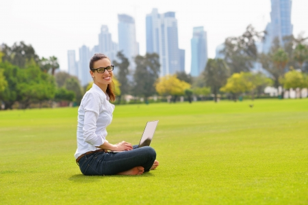 happy young student woman with laptop in city park study photo