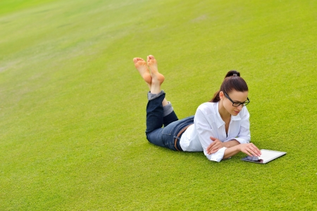 lying on grass: Beautiful young student  woman study with tablet in park