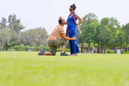 Happy pregnant woman with his husband at beautiful sunny day in park photo