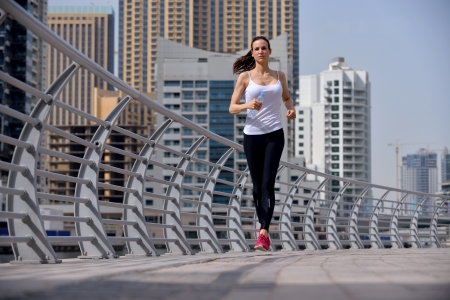 Running in city park  Woman runner outside jogging at morning with Dubai urban scene in background photo