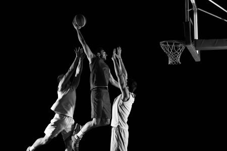 basket-ball joueur de jeu de sport dans l'action isolée sur fond noir Banque d'images