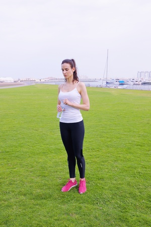 Young beautiful  woman jogging and running  on morning at  park in the city. Woman in sport outdoors health and fitness concept photo