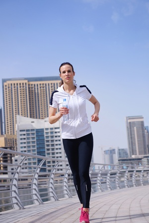 Running in city park. Woman runner outside jogging at morning with Dubai urban scene in background photo