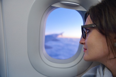happy young  tourist  woman is sitting in the airplane looking window and travel to summer vacation photo