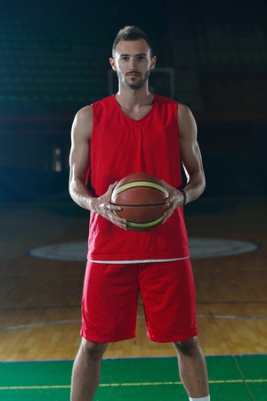 Basketball player portrait  on basketball court holding ball with black isolated background photo