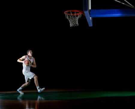 黒の背景上に分離されてアクションのバスケット ボール ゲーム スポーツ選手
