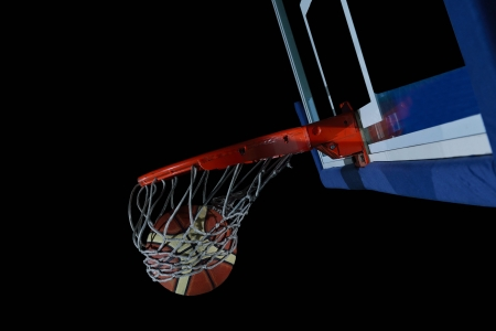 street shots: Basketball ball,  board and net  on black background in gym indoor