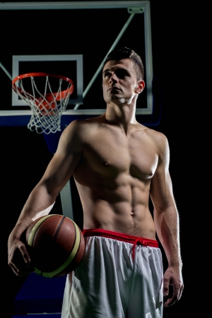 boy basketball: Basketball player portrait  on basketball court holding ball with black isolated background