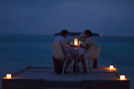 romantic evening with wine: romantic couple  in love have dinner in outdoor restaurant with candles with sea in background Stock Photo