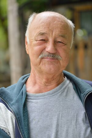 Portrait of smiling elderly man outdoor in nature photo