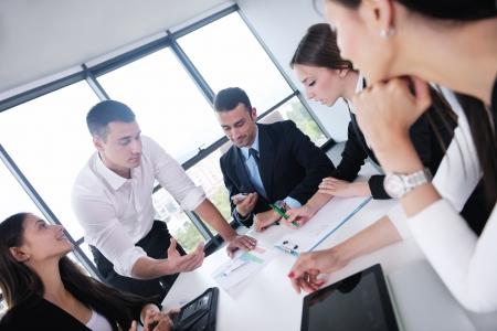 オフィスでの会議で幸せな若いビジネス人々 のグループ