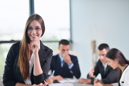 happy young business woman  with her staff,  people group in background at modern bright office indoors Stock Photo - 22105495