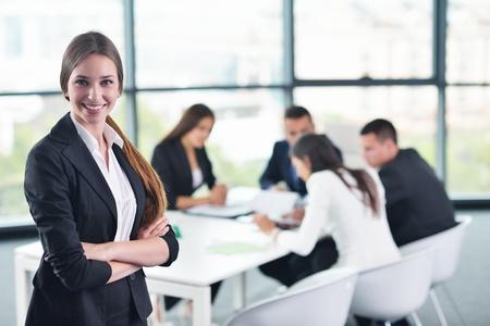 formacion empresarial: joven mujer de negocios feliz con su equipo, el grupo de personas al fondo ya la moderna oficina brillantes interiores Foto de archivo