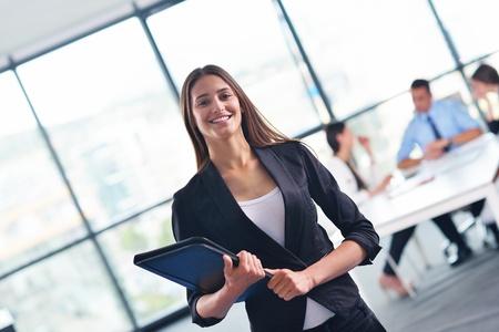 büro: kapalı modern, aydınlık ofiste arka planda onun personeli, insanlar grubu ile mutlu genç iş kadını